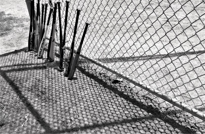 Photo of bats leaning against fence, surrounded by lines and patterns. Image in black and white.